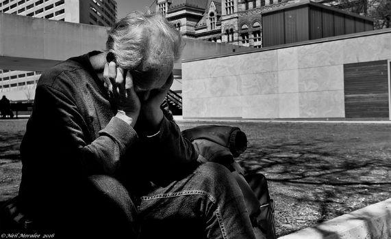 Hombre mayor sentado en el suelo con la cara semitapada