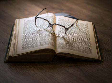 Libro abierto con unas gafas encima.