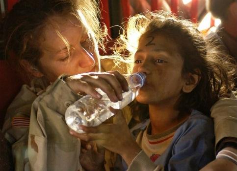 Mujer dando agua a niña