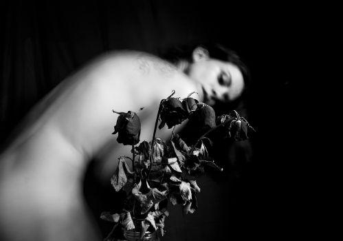 Chica desnuda encorvada y ramos de flores marchitas