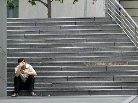 Persona mirando el móvil en escalera