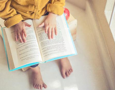 Niño pequeño leyendo un libro.