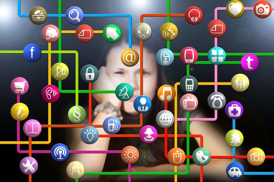 como influyen las nuevas tecnologias en los adolescentes, chica frente a pantalla con iconos nuevas tecnologías