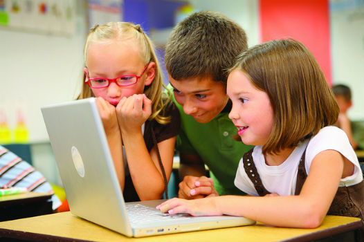 Niños con ordenador compartiendo intereses