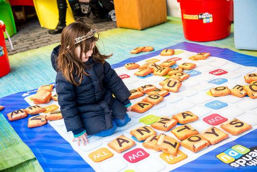 Niña jugando con Scrabbel gigante