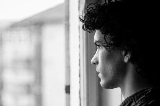 Chico joven mirando por la ventana.