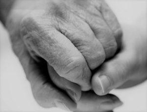 prevención del maltrato en la vejez, manos unidas de un anciano y de una persona joven