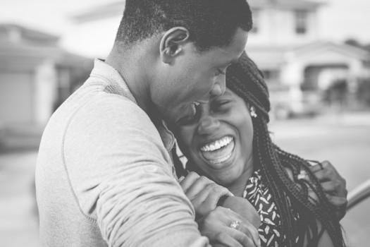 Hombre y mujer en pareja sonríen como al disfrutar de un momento juntos.