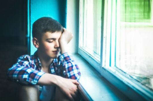 acoso escolar, bullying, niño triste en una ventana