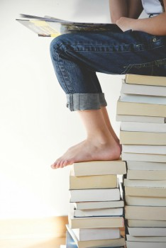 procrastinar, persona leyendo sobre pila de libros