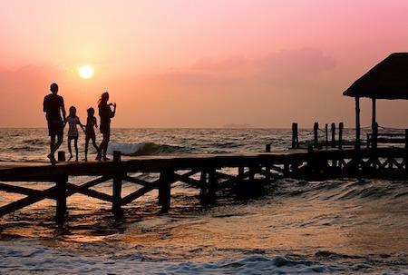 Salud física y mental en verano, compartir en familia, familia en puente sobre la playa