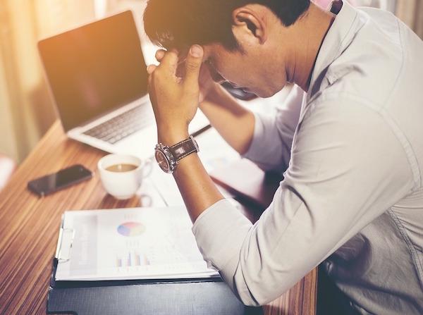 sindrome postvacacional, sintomas, chico cansado en mesa de trabajo